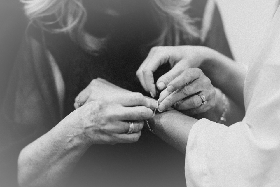 Mother helping bride with wedding bracelet