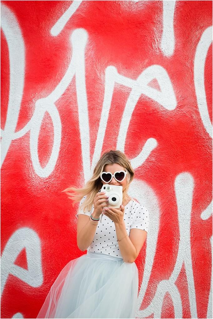 Tutu in front of LOVE ME graffiti wall